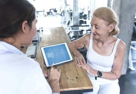 Doctor with senior woman in rehabilitation center check health care and showing data something on Tablet. 스톡 콘텐츠