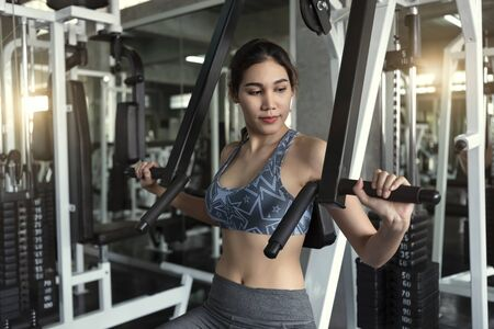 Young asian woman lifting barbell in gym. healthy lifestyle and workout motivation concept.