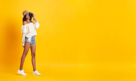 Cheerful young african woman dressed in summer clothes holding camera shooting over yellow background with copy space.