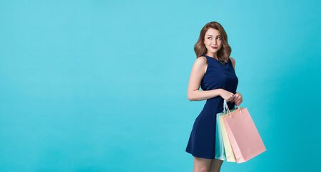 Happy beautiful young woman in blue dress and hand holding shopping bag at copy space isolated over blue background. 스톡 콘텐츠