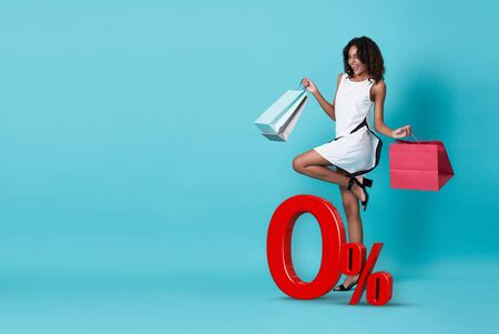 Happy beautiful young african woman in white dress and hand holding shopping bag with 0% interest installment payment plan isolated over blue background.