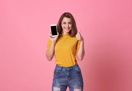 Portrait of happy young woman showing at blank screen mobile phone isolated over pink background.
