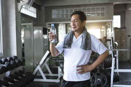 asian senior man thirsty drinking water after exercise in fitness gym. elderly healthy lifestyle.