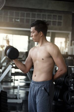 Young asian man lifting dumbbells in gym. healthy lifestyle and workout motivation concept. 스톡 콘텐츠