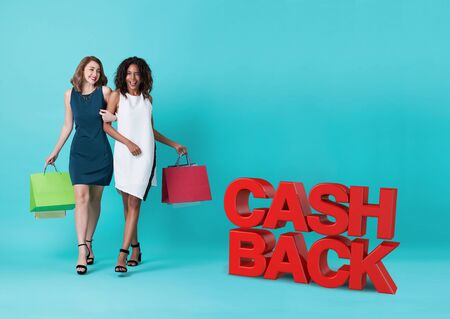Two happy young woman hand holding shopping bag with cashback promotion isolated over blue background. 스톡 콘텐츠