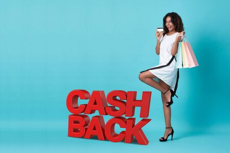 Happy young african woman showing credit card and shopping bag with cashback promotion isolated over blue background. 스톡 콘텐츠