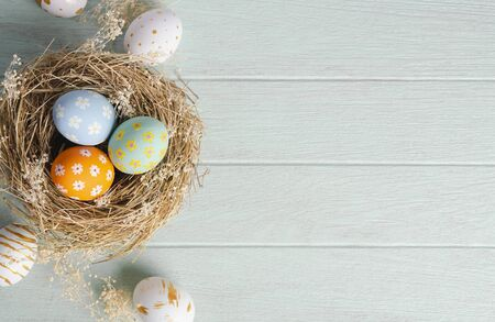 Happy easter, Easter painted eggs in nest on wooden rustic table for your decoration in holiday. Top view with copy space.