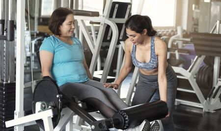 Trainer with asian senior woman lifting barbell in gym. healthy lifestyle and workout concept.