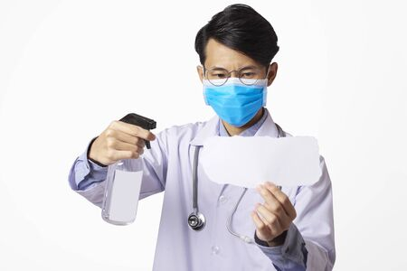Asia doctor using spray alcohol cleaning mockup paper for protect anti virus bacteria. Stock Photo