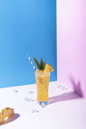 iced pineapple punch cocktail in glass on color background. summer drink.