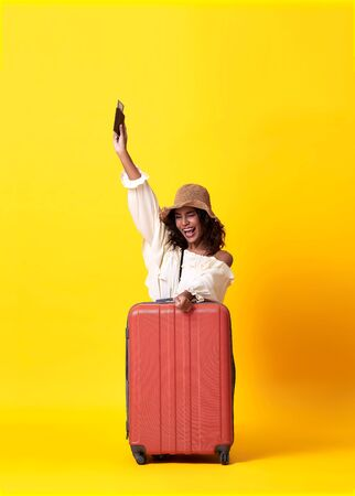 Cheerful young african woman dressed in summer clothes holding passport with suitcase over yellow background.