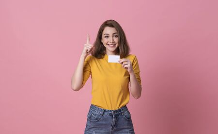 Young smiling beautiful woman in yellow shirt showing credit card in hand over pink background. Stock fotó - 147814706
