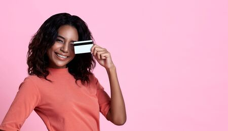 Young smiling beautiful african woman showing credit card in hand over pink banner background with copy space. Stock fotó - 148009513