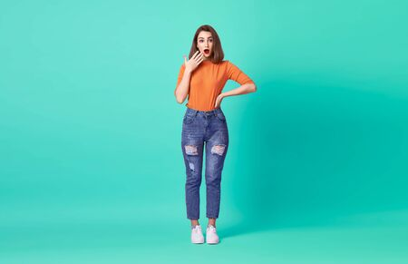 Shocked excited beautiful woman with mouth open wearing casual orange t-shirt over blue background.