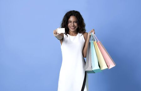 Portrait of an excited beautiful african women wearing white dress and credit card holding shopping bags isolated on blue background. Stockfoto