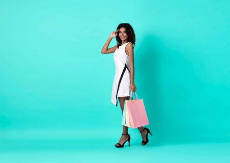 Happy beautiful african woman in white dress and hand holding shopping bag isolated over blue background.