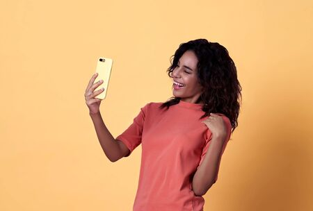 Portrait of a happy young african woman selfie celebrating with mobile phone isolated over yellow background.