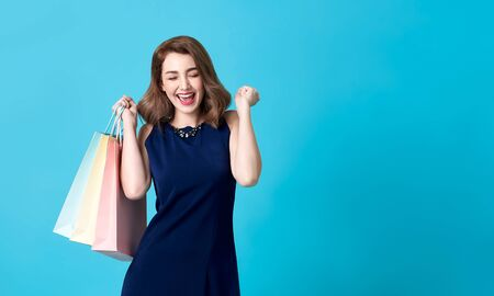 Portrait of an excited beautiful woman wearing blue dress and holding shopping bags isolated on blue background. Stockfoto