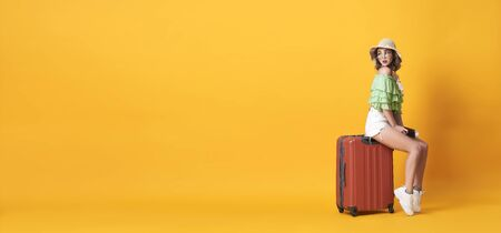 Cheerful young woman dressed in summer clothes holding passport with suitcase over yellow banner background with copy space. Stockfoto