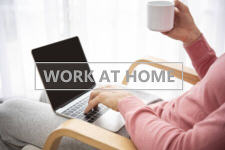 man wearing clothing comfortable working on laptop computer while sitting and drinking coffee at the living room. work at home concept.