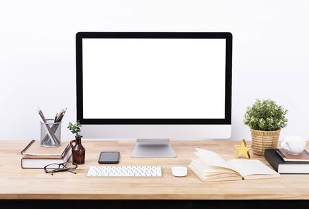 Mockup Blank screen desktop computer and decorations on wood table and white wall background.