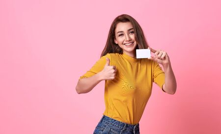 Young smiling beautiful woman in yellow shirt showing credit card in hand over pink background. Stock fotó - 147815125