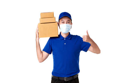 Asian delivery man wearing face mask in blue uniform standing with carry parcel post box isolated over white background. express delivery service during covid19.