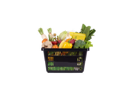 Black plastic grocery basket full of healthy vegetables and fruits,  ingredients isolated on white background Stockfoto