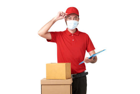 Asian delivery man wearing face mask in red uniform standing with parcel post box isolated over white background. express delivery service during covid19.