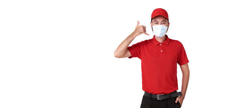 Asian delivery man wearing face mask in red uniform and making call gesture isolated over white background. Stockfoto
