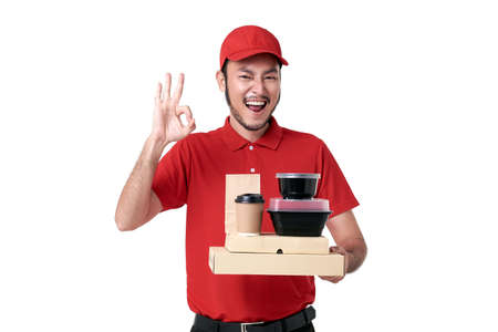Asian delivery man wearing in red uniform holding lunch box and takeaway coffee isolated over white background. express delivery service during covid19. Stockfoto