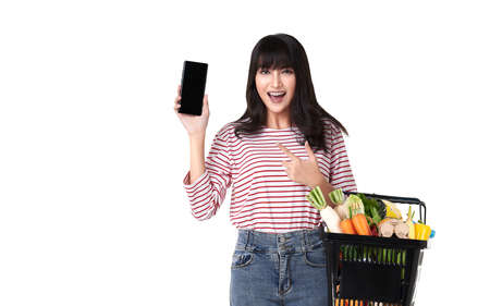 Happy Asian woman with smartphone holding basket full of fresh vegetable groceries isolated on white background.