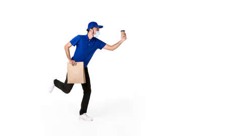 Asian delivery man wearing face mask in blue uniform running with paper bag and takeaway coffee isolated over white background. express delivery service during covid19.