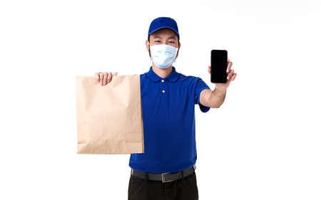 Asian delivery man wearing face mask in blue uniform with smart phone holding paper bag isolated on white background. express delivery service during covid19. Stockfoto