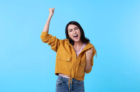 Cheerful young Asian woman raising his fists with smiling delighted face, yes gesture, celebrating success on blue background. Stockfoto
