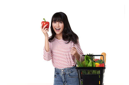 Happy smiling Asian woman holding basket shopping full of vegetables isolated on white background.