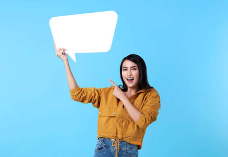 Smiling happy asian woman holding blank speech bubble and with empty space for text on blue background.