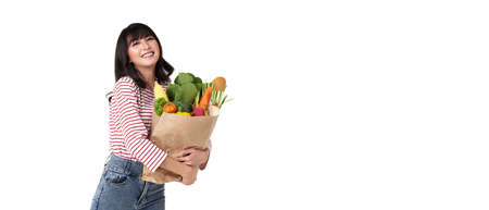 Happy smiling Asian woman holding paper shopping bag full of vegetables isolated on banner background with copy space. Standard-Bild