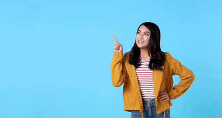 Smiling happy asian woman with her finger pointing isolated on light blue banner background with copy space.