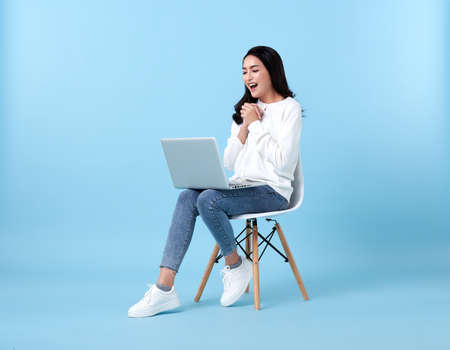 Young woman asian happy smiling in casual white cardigan with denim jeans.While her using laptop sitting on white chair isolate on bright blue background. Stockfoto
