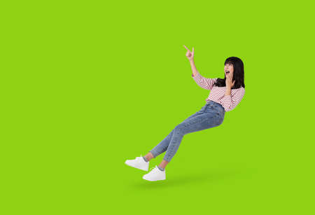 Young beautiful smiling and surprise asian girl floating in mid air with hand pointing up to copy space isolated on green background. Stockfoto - 152465970
