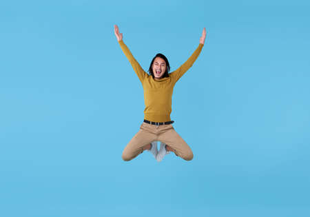 Happy energetic young Asian man jumping in mid-air isolated on blue background.