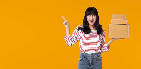 Happy casual asian woman carrying a delivery box that has been packaged for shipping. ready to point  finger in the blank space isolated on bright orange background. Stockfoto