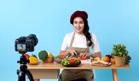 Happy asian young woman in fashion look style and shooting video with camera cooking food healthy is blogger presenting for social people.Her is influencer in social online.