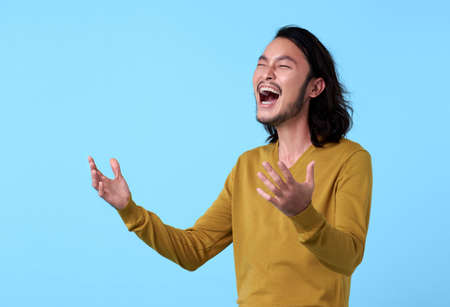 Young Asian man happy with laugh face on blue background.
