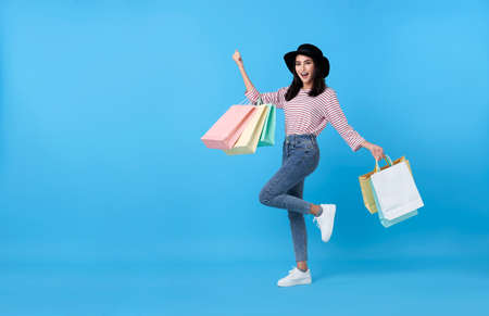 Happy young thai asian female carrying with both arms raised in a ecstatic gesture and shopping bags on blue copy space background. Stockfoto