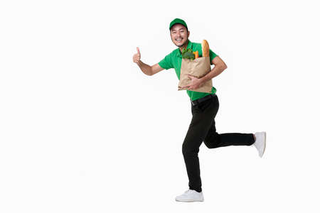 Asian delivery man wearing in green uniform holding fresh food paper bag isolated over white background. Stockfoto