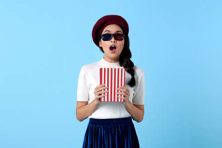 Excited Asian woman wearing 3d glasses gasping and holding popcorn while watching movie. Stockfoto - 153210303