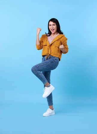 Happy asian woman in yellow shirt having fun and looking at the camera over blue background. Stockfoto - 153361099