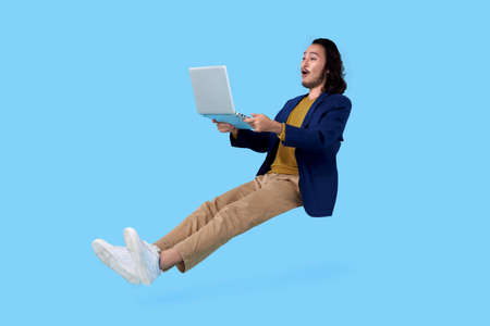 Young asian businessman hand holding computer laptop floating in mid-air isolated on blue background.